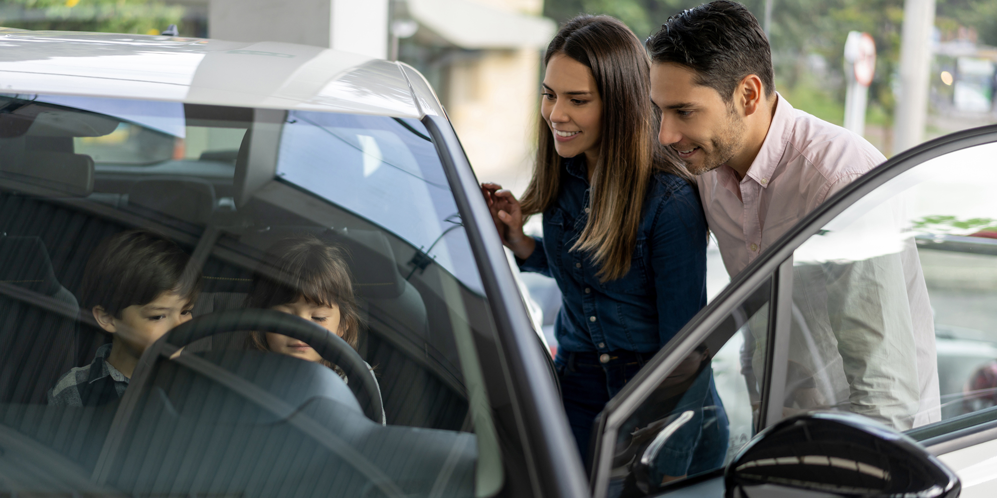 Man and Woman Smiling Outside Car with Two Children in Driver Seat