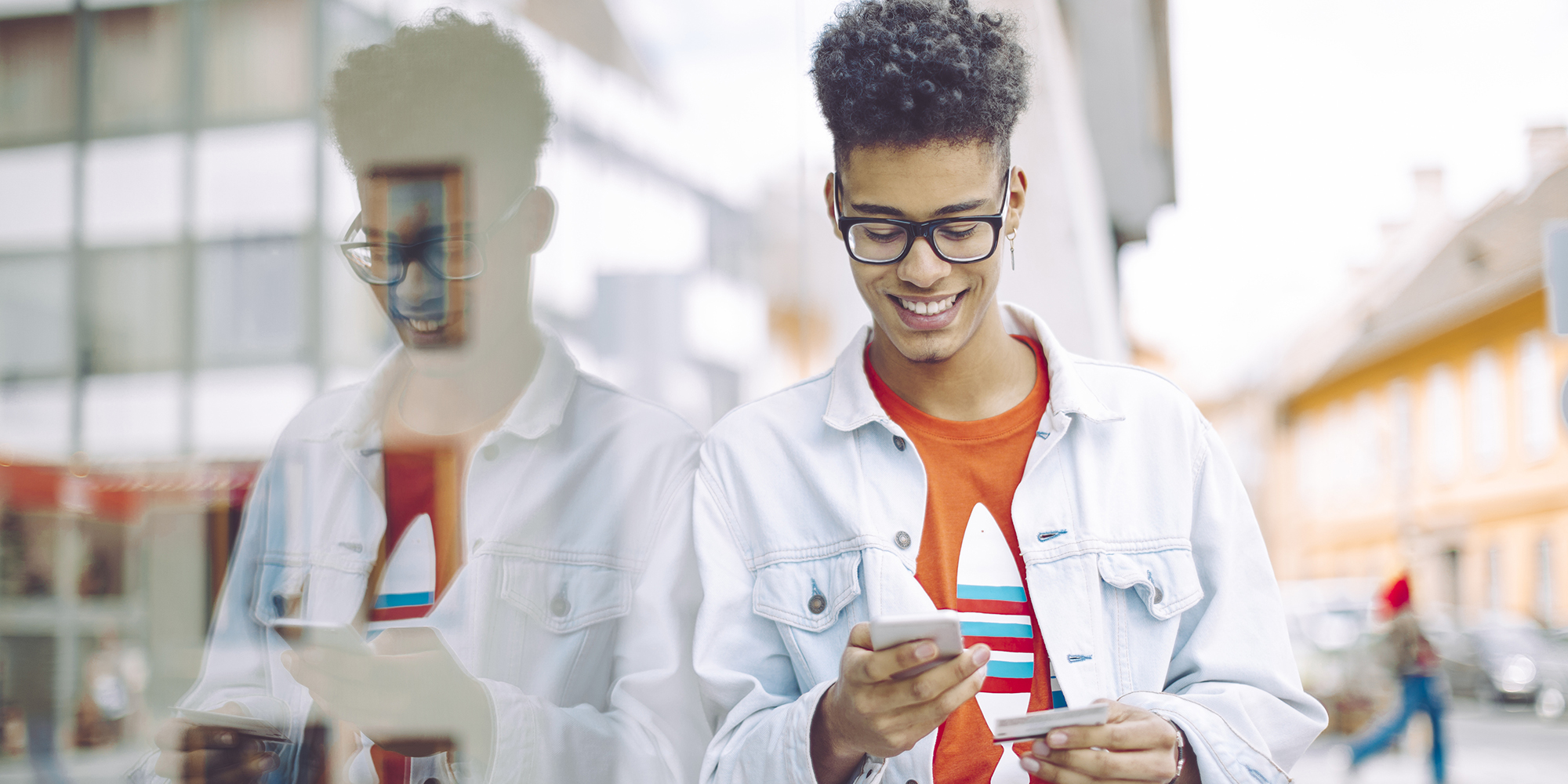Young Man Smiling and Using Smartphone and Credit Card on City Street