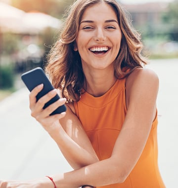 Woman in Orange Dress Smiling with Smartphone