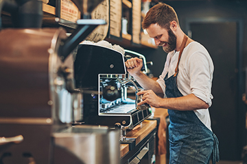Smiling Millennial Barrista Pouring Cup of Coffee