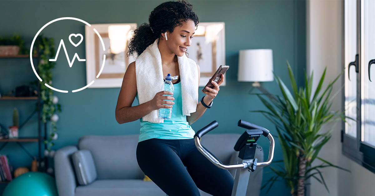 Young Woman Sitting on Exercise Bike, Checking Phone and Smiling