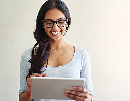 Woman Standing, Smiling and Checking Tablet