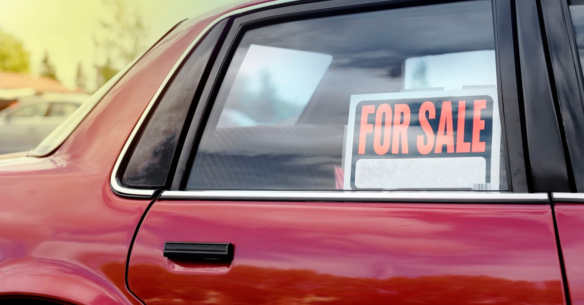 "Red Car with ""For Sale"" Sign in Passenger Side Window"